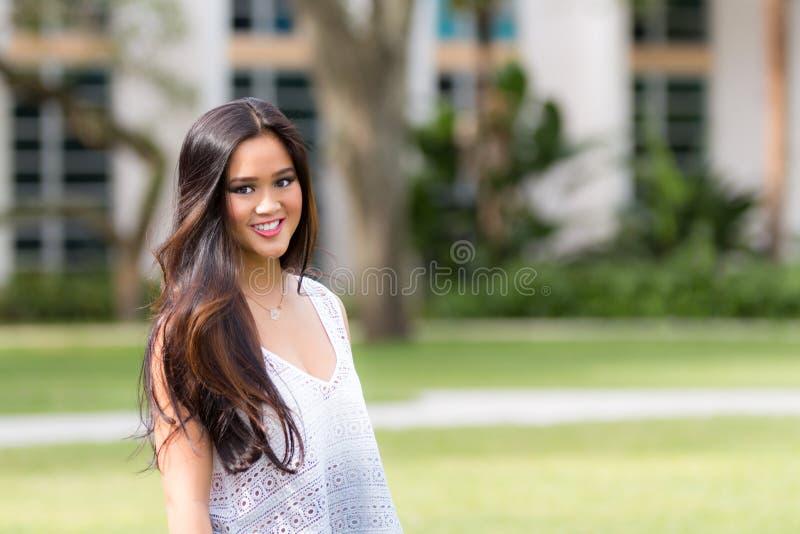 Retrato de uma menina asiática bonita nova de sorriso com marrom longo ha fotografia de stock royalty free