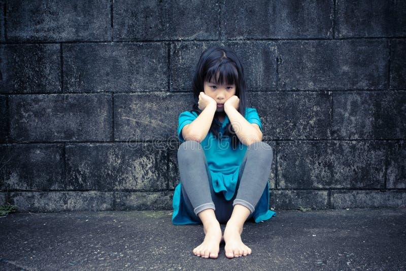 Retrato de uma menina asiática triste contra a parede do grunge foto de stock royalty free
