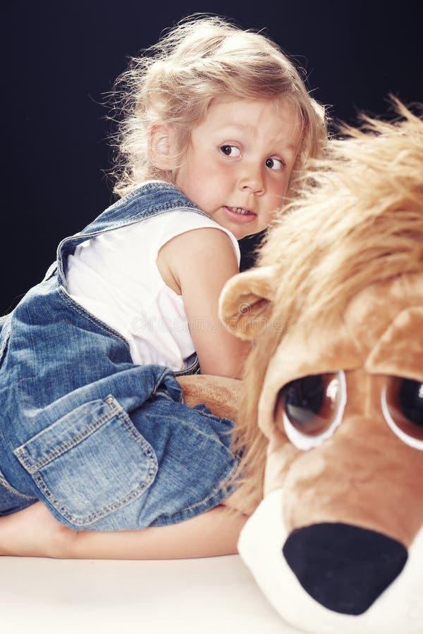 Retrato de uma menina assustado em macacões da sarja de Nimes, sentando-se em um estúdio no fundo preto foto de stock royalty free