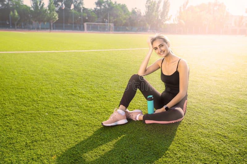 Retrato de uma menina atrativa com uma figura desportiva que senta-se na grama O modelo senta-se em um campo de esportes com uma  imagens de stock