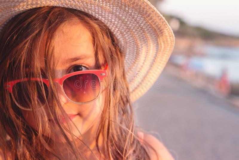 Retrato de uma menina bonita com óculos de sol e chapéu de palha na praia foto de stock royalty free