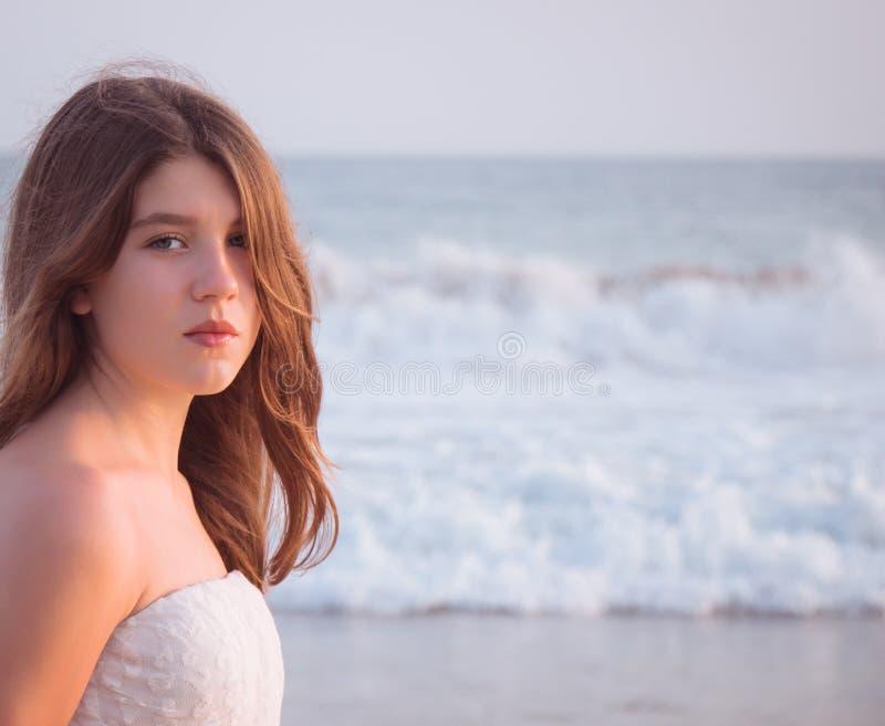 Retrato de uma menina bonita com as ondas de oceano no fundo foto de stock royalty free