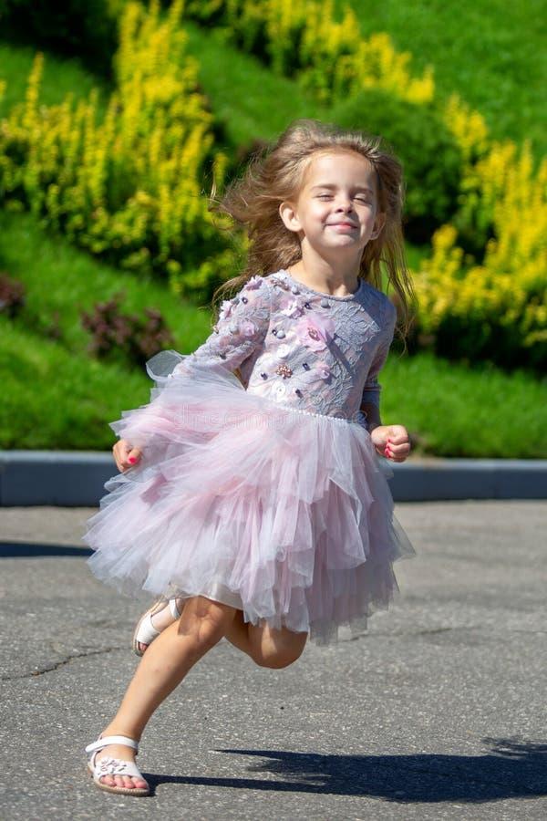 Retrato de uma menina bonita com cabelo longo luxuoso fora Criança running imagens de stock royalty free