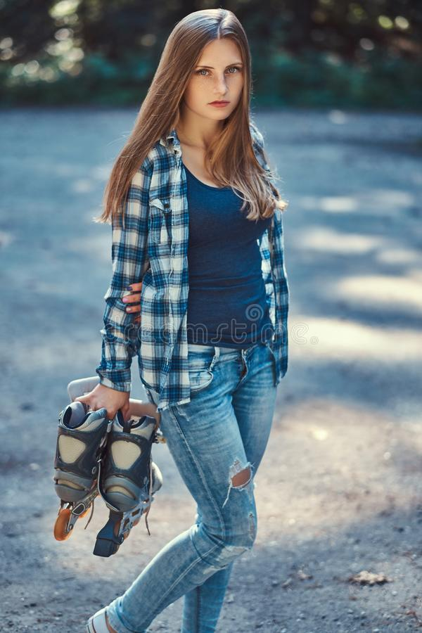 Retrato de uma menina bonita com a camisa do velo do cabelo longo e as calças de brim vestindo, rolos das posses fotos de stock