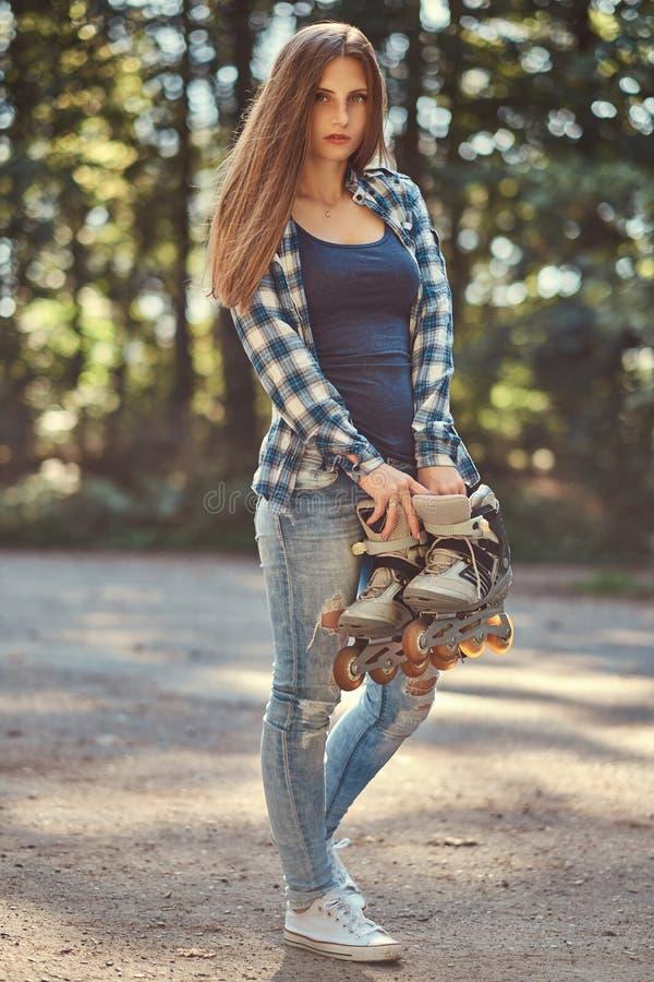 Retrato de uma menina bonita com a camisa do velo do cabelo longo e as calças de brim vestindo, rolos das posses foto de stock royalty free