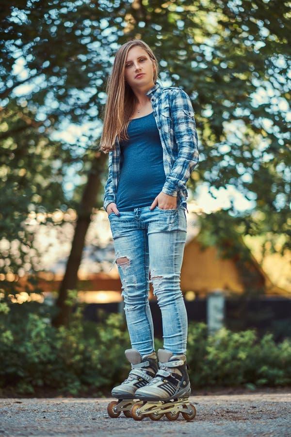 Retrato de uma menina bonita com a camisa e as calças de brim vestindo do velo do cabelo longo nos rolos, estando no parque no ve foto de stock