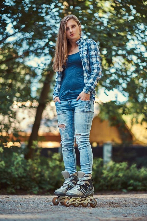 Retrato de uma menina bonita com a camisa e as calças de brim vestindo do velo do cabelo longo nos rolos, estando no parque no ve fotos de stock