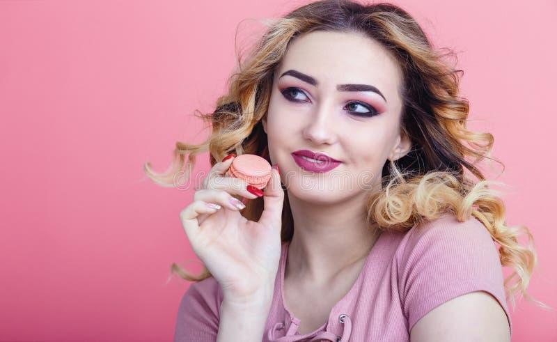 Retrato de uma menina bonita com o bolinho de am?ndoa nas m?os em um fundo brilhante da cor, conceito de anunciar o alimento, die imagens de stock