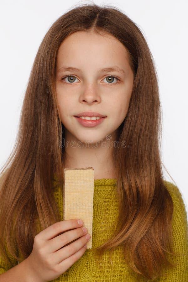 Retrato de uma menina bonita da crian?a de 8 anos em uma camiseta e com uma bolacha em sua m?o Fundo branco imagens de stock