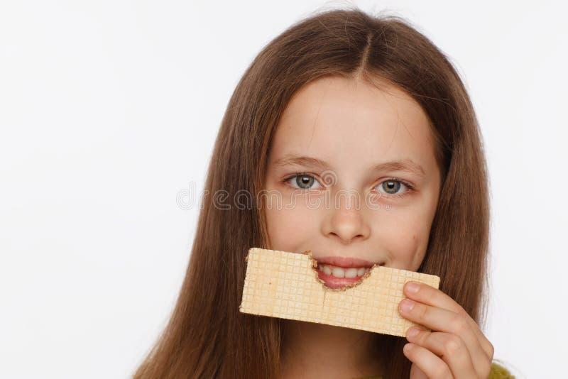 Retrato de uma menina bonita da crian?a de 8 anos em uma camiseta e com uma bolacha em sua m?o Fundo branco fotos de stock royalty free