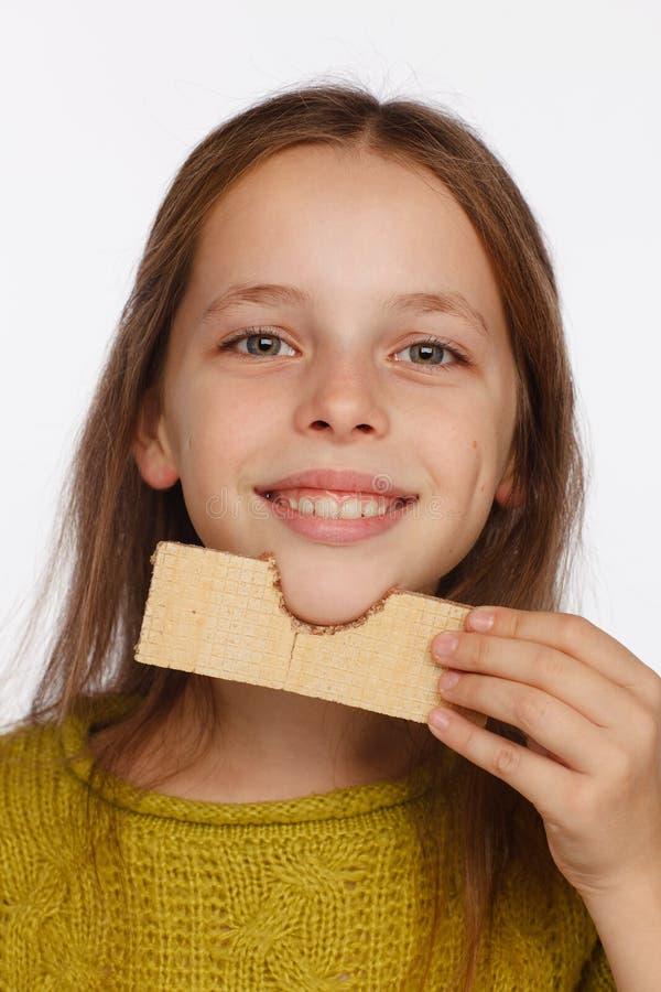 Retrato de uma menina bonita da crian?a de 8 anos em uma camiseta e com uma bolacha em sua m?o Fundo branco fotografia de stock