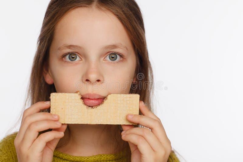 Retrato de uma menina bonita da crian?a de 8 anos em uma camiseta e com uma bolacha em suas m?os Fundo branco imagens de stock