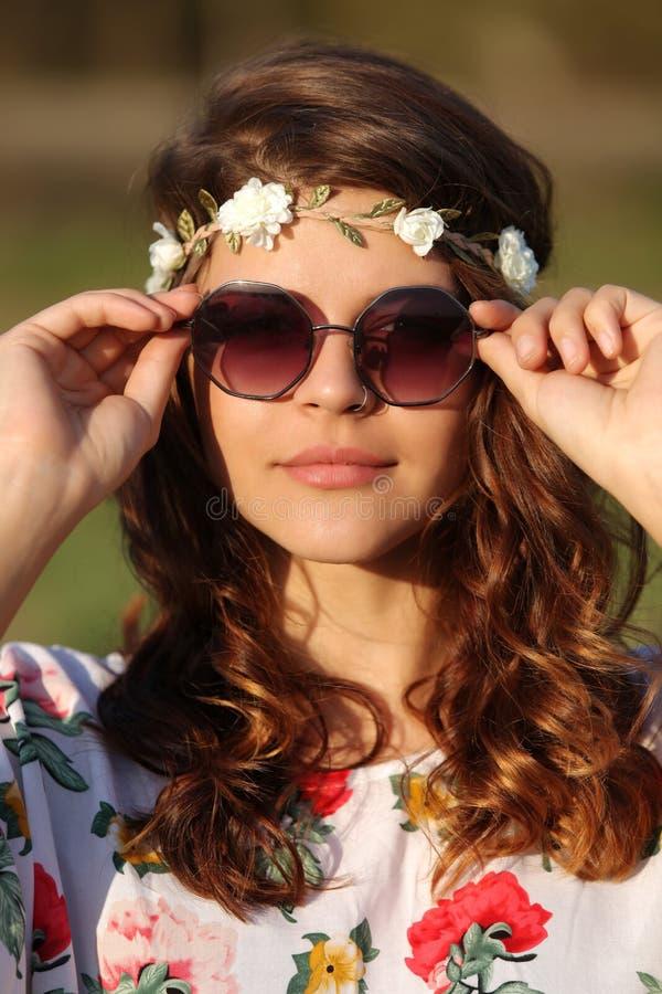 Retrato de uma menina bonita da hippie que entregue guardar óculos de sol fora imagens de stock royalty free