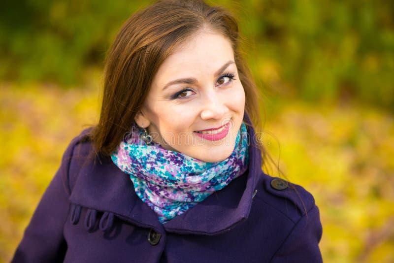 Retrato de uma menina bonita de sorriso no fundo obscuro das folhas de outono fotografia de stock