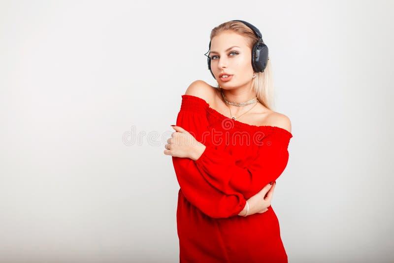 Retrato de uma menina bonita do DJ dos jovens com fones de ouvido em um vermelho imagens de stock