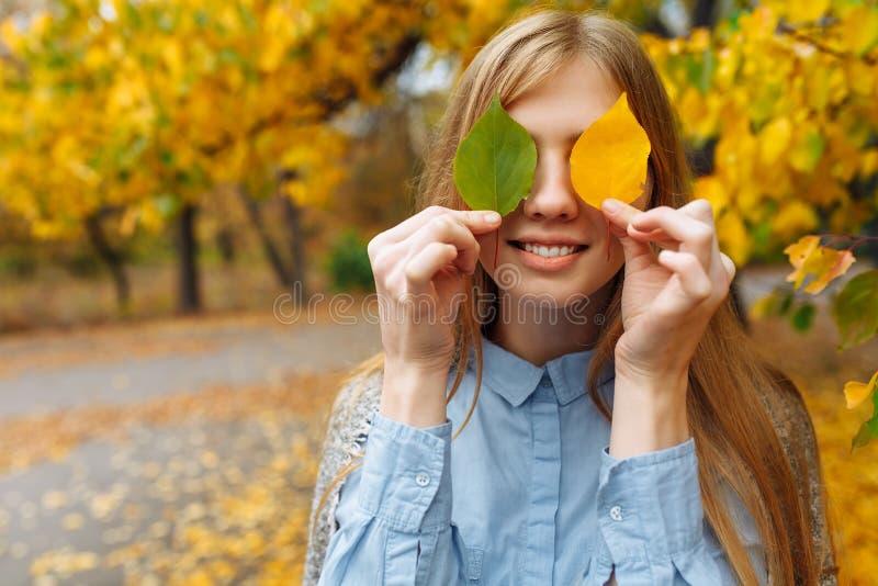 Retrato de uma menina bonita, doce, alegre que ande no parque na estação do outono foto de stock royalty free