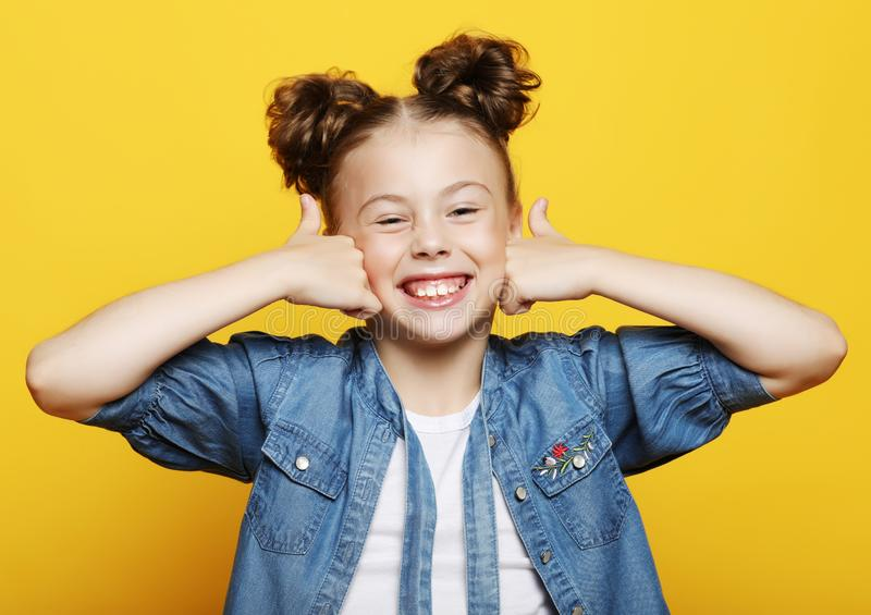 Retrato de uma menina bonita e segura que mostra os polegares acima fotos de stock