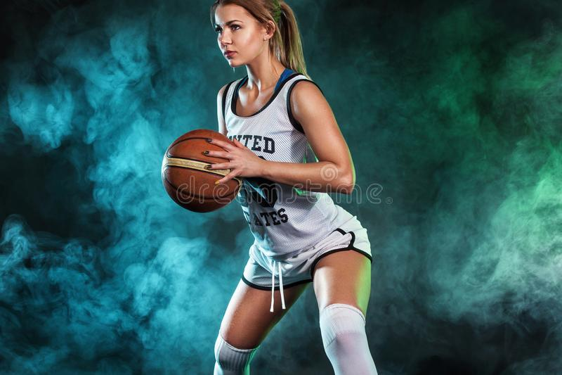 Retrato de uma menina bonita e 'sexy' com um basquetebol no estúdio Conceito do esporte foto de stock