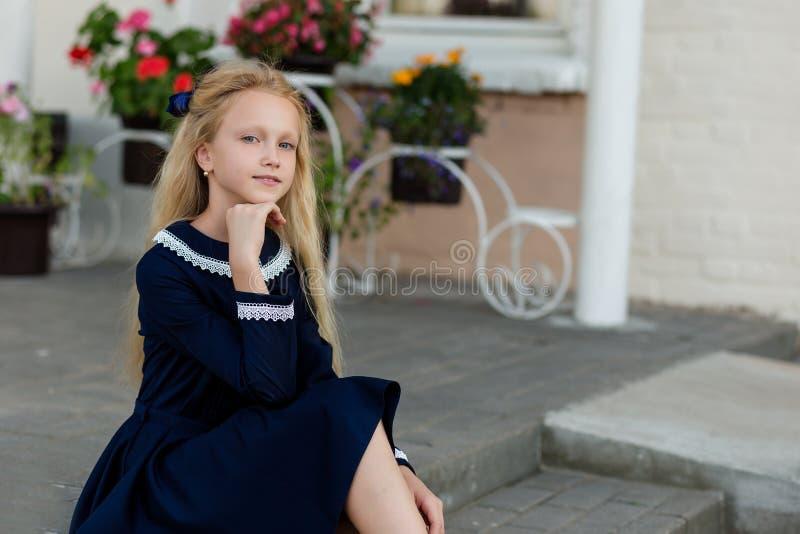 Retrato de uma menina bonita em uma farda da escola antes da classe em imagem de stock royalty free