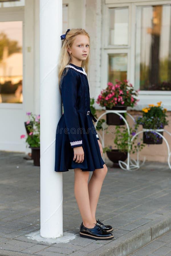 Retrato de uma menina bonita em uma farda da escola antes da classe em fotos de stock