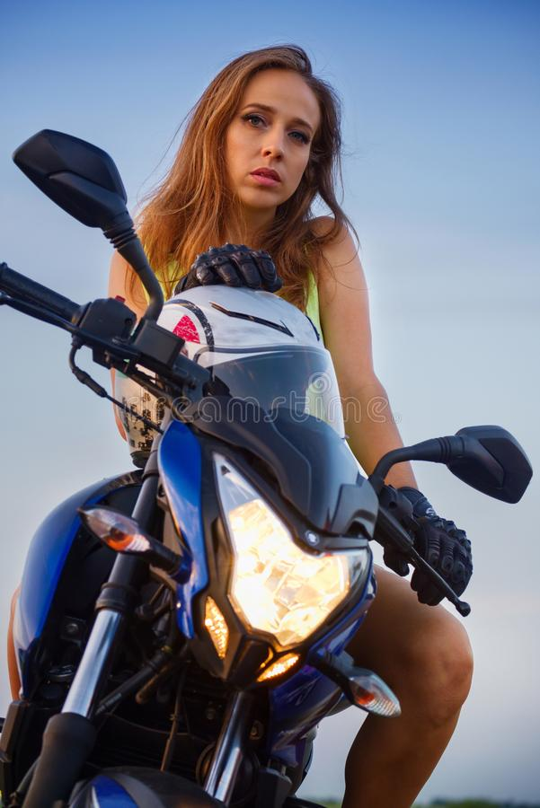 Retrato de uma menina bonita em uma motocicleta do esporte imagens de stock