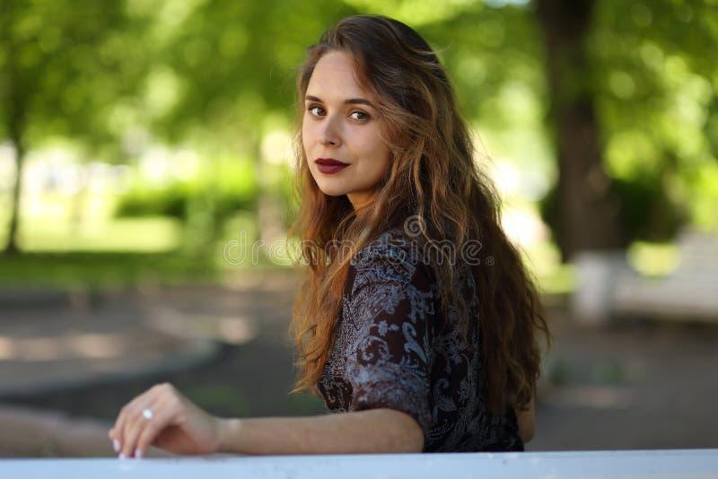 Retrato de uma menina bonita em um banco de parque imagens de stock