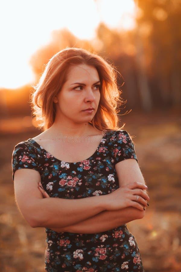 Retrato de uma menina bonita em um campo em um fundo do por do sol fotos de stock royalty free