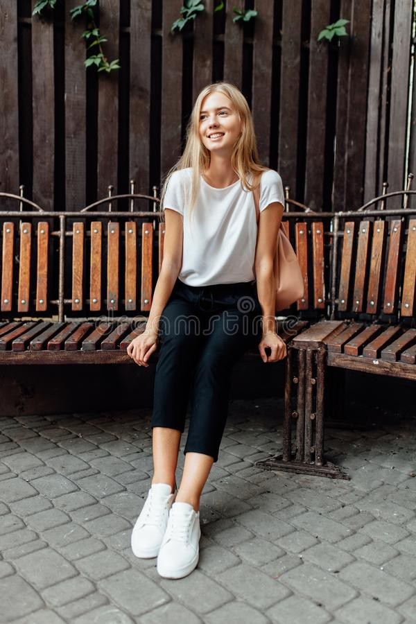 Retrato de uma menina bonita em um t-shirt branco que senta-se em um ben imagens de stock