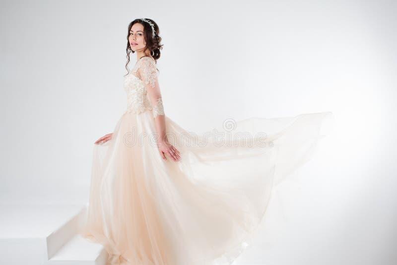 Retrato de uma menina bonita em um vestido de casamento A noiva em um vestido luxuoso que está nas escadas, escala acima fotografia de stock