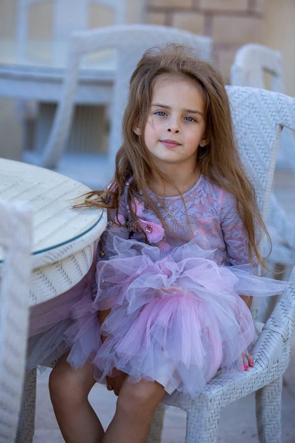 Retrato de uma menina bonita fora Criança em uma tabela em um café imagem de stock