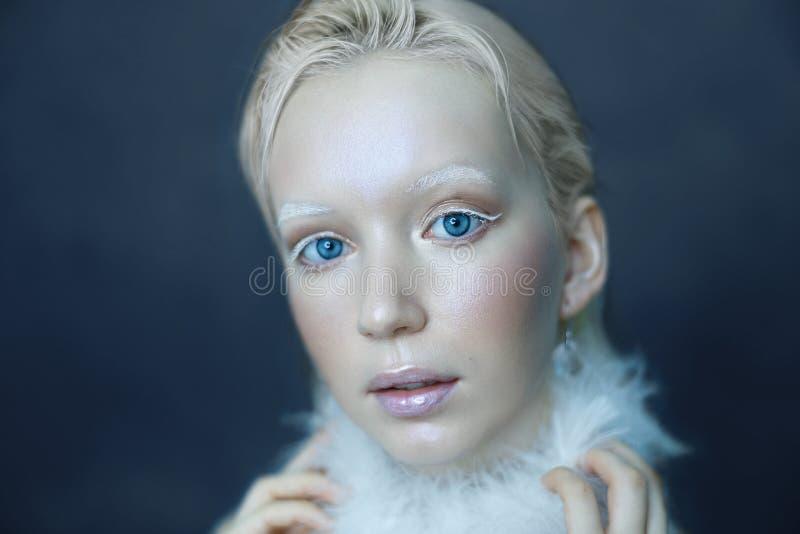 Retrato de uma menina bonita na geada em sua cara em um fundo azul do gelo fotos de stock