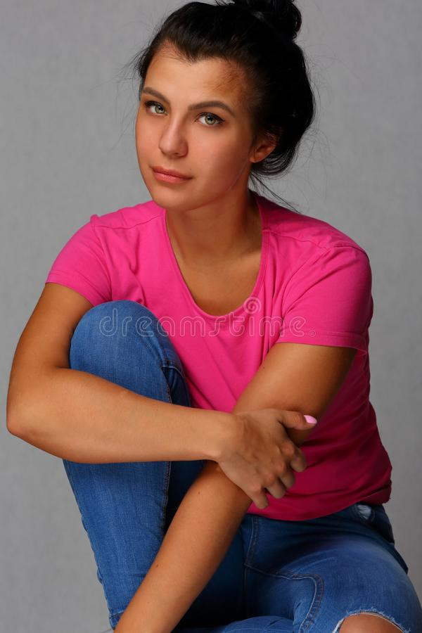 Retrato de uma menina bonita nas calças de brim e no t-shirt imagem de stock