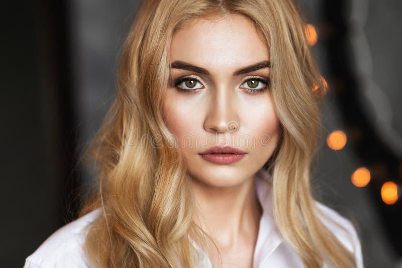 Retrato de uma menina bonita nova em uma camisa branca que olha na câmera imagem de stock royalty free