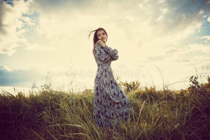 Retrato de uma menina bonita nova em um vestido longo que está em t foto de stock