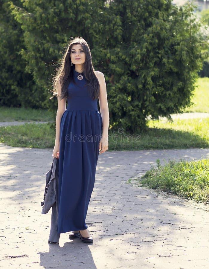 Retrato de uma menina bonita nova no vestido azul foto de stock