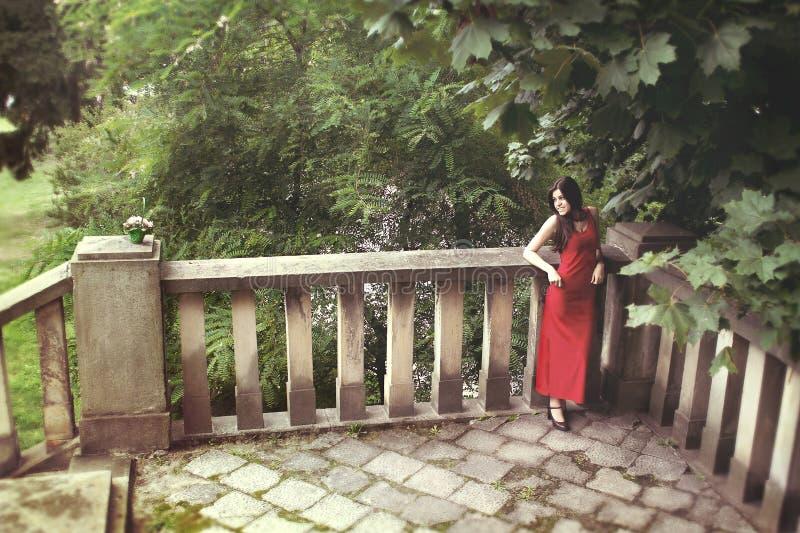 Retrato de uma menina bonita nova no vestido vermelho foto de stock