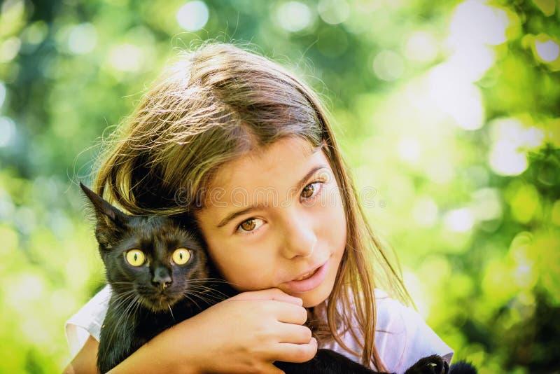 Retrato de uma menina bonita que guarda um gato preto fotografia de stock royalty free