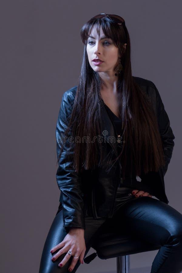 Retrato de uma menina bonita 'sexy' com cabelo longo na roupa de couro preta Fotografia da forma do estúdio Fundo cinzento imagem de stock royalty free