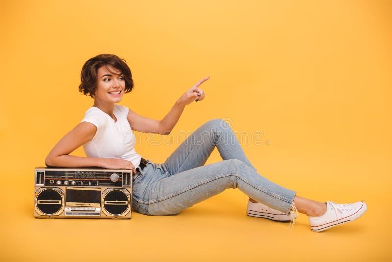 Retrato de uma menina bonita de sorriso que senta-se com jogador de registro foto de stock royalty free