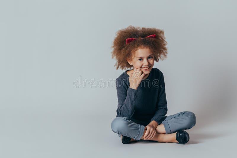 Retrato de uma menina bonita de sorriso que senta-se no assoalho Fundo cinzento fotografia de stock royalty free