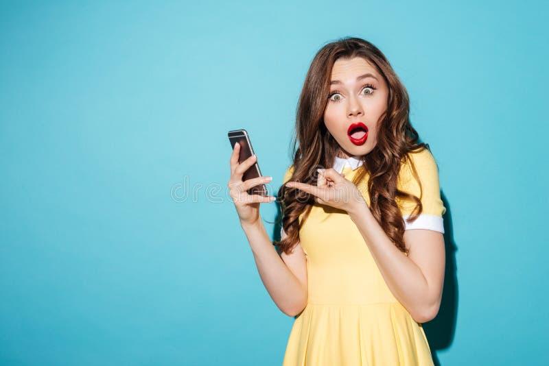 Retrato de uma menina bonito confusa em apontar do vestido imagem de stock