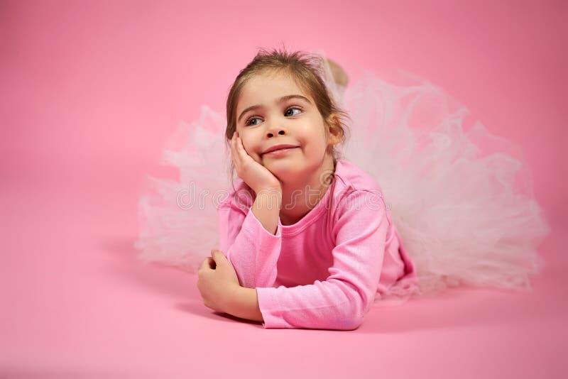 Retrato de uma menina bonito na saia do tule em um fundo cor-de-rosa fotografia de stock royalty free