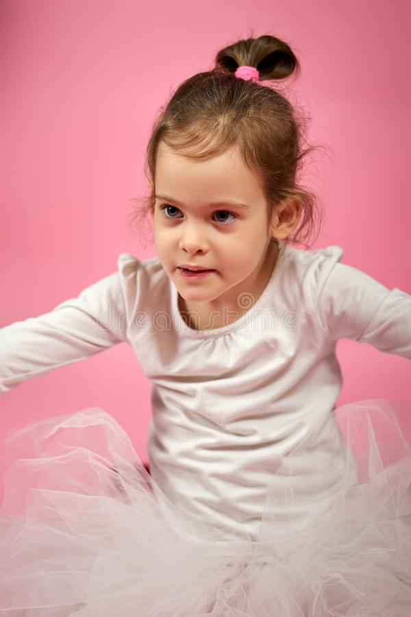 Retrato de uma menina bonito na saia do tule em um fundo cor-de-rosa imagens de stock