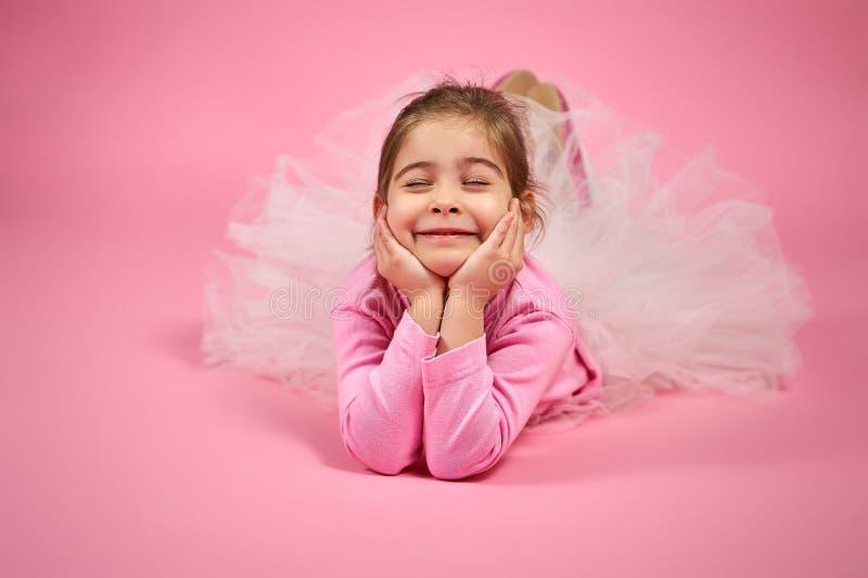 Retrato de uma menina bonito na saia do tule em um fundo cor-de-rosa imagem de stock