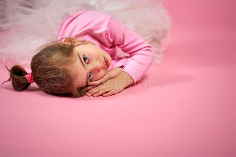 Retrato de uma menina bonito na saia do tule em um fundo cor-de-rosa foto de stock royalty free