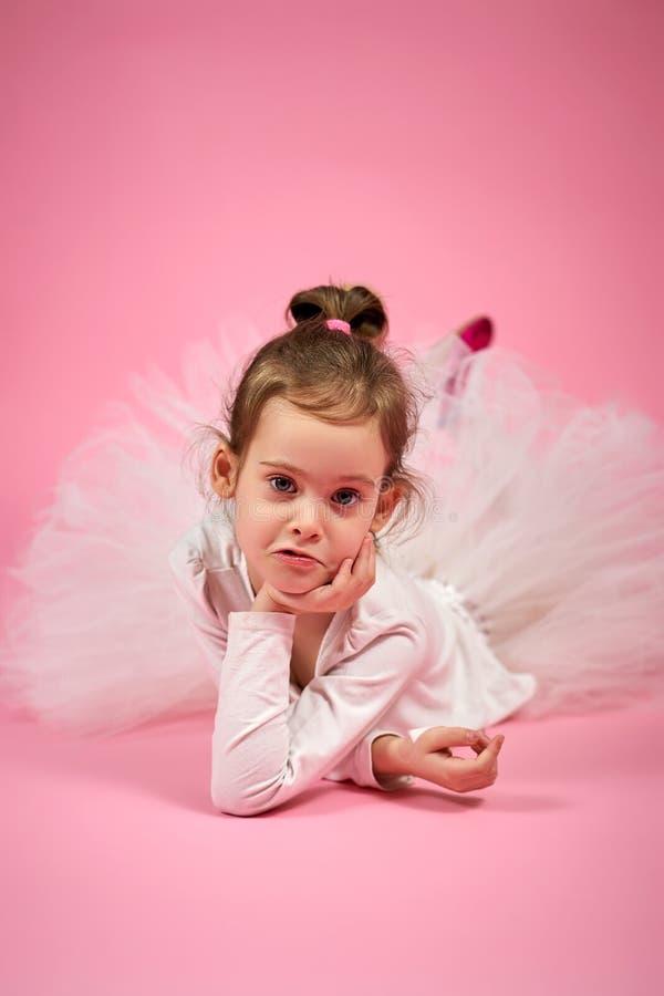 Retrato de uma menina bonito na saia do tule em um fundo cor-de-rosa imagens de stock royalty free