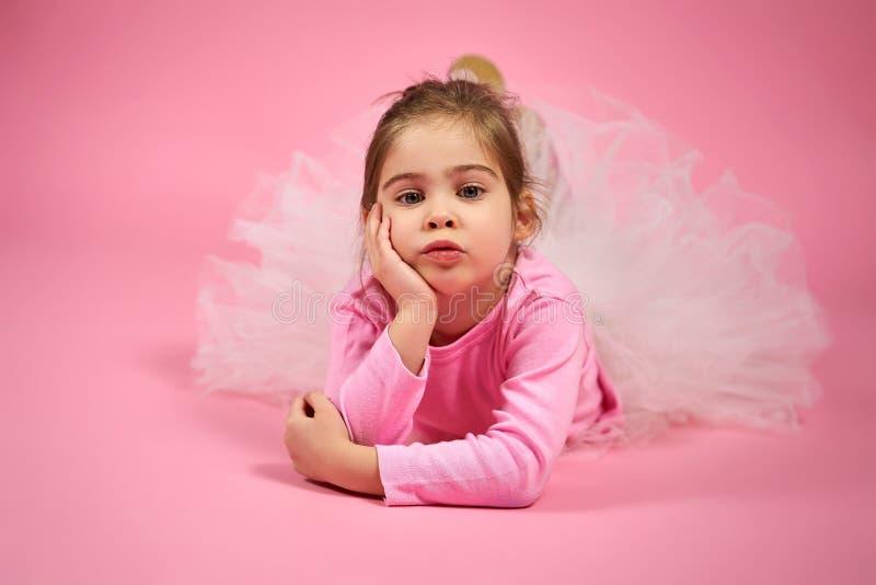 Retrato de uma menina bonito na saia do tule em um fundo cor-de-rosa fotos de stock royalty free