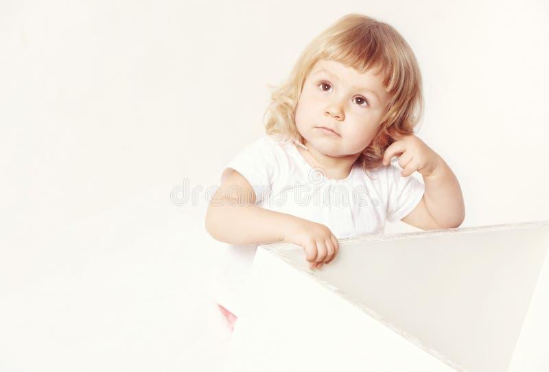 Retrato de uma menina bonito pensativa em um vestido branco no fundo branco fotografia de stock royalty free
