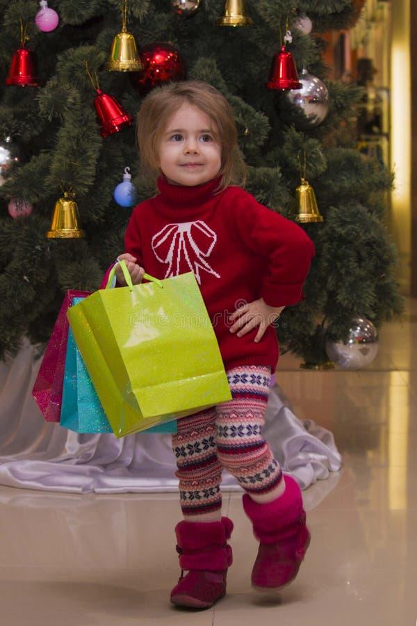 Retrato de uma menina bonito pequena que guarda pacotes com os presentes no fundo de uma árvore de Natal shopping sobre fotos de stock royalty free
