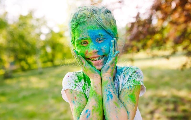 Retrato de uma menina bonito pintada nas cores do festival de Holi imagem de stock royalty free